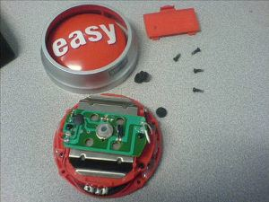 Image of a broken electronic easy button in pieces.